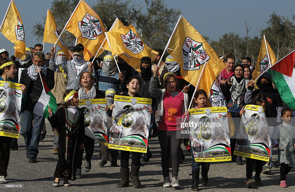 Palestinian protesters carry Fatah party flags during a march organised by residents of the West Bank village Nabi Saleh to protest against the expansion of Jewish settlements on Palestinian land, on January 4, 2013 . Hundreds of thousands of supporters of Palestinian president Mahmud Abbas's Fatah party on Friday held a mass rally in Gaza, their first since Hamas seized control of the territory in 2007. MOMANI