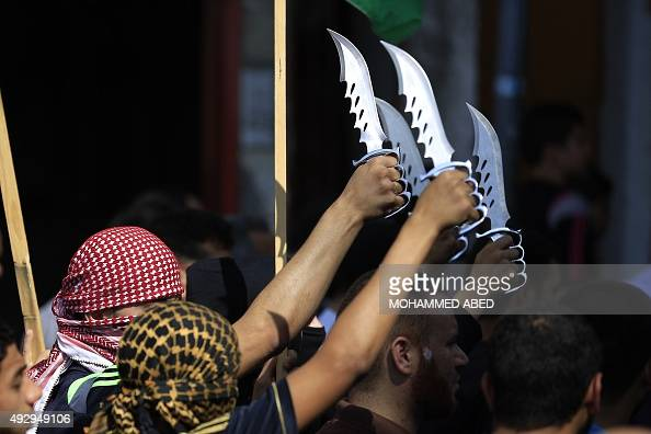 Palestinian protesters carry knives during a demonstration in the Jabalia refugee camp in northern Gaza on October 16 2015 Palestinians called for a...