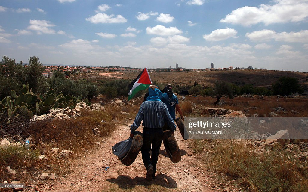 Palestinian protesters carry tires during a demonstration against Israeli settlements and its separation wall, in the West Bank village of Nilin, on June 14, 2013.