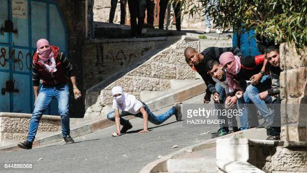 TOPSHOT Palestinian protesters clash with Israeli security forces during a demonstration calling for the opening of Shuhada Street which is largely...