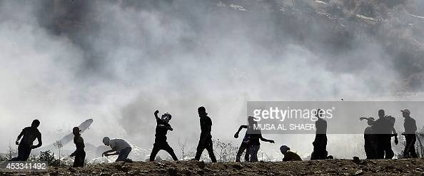 Palestinian protesters clash with Israeli security forces following a demonstration in support of Gaza after Friday prayers at the Hawara checkpoint...
