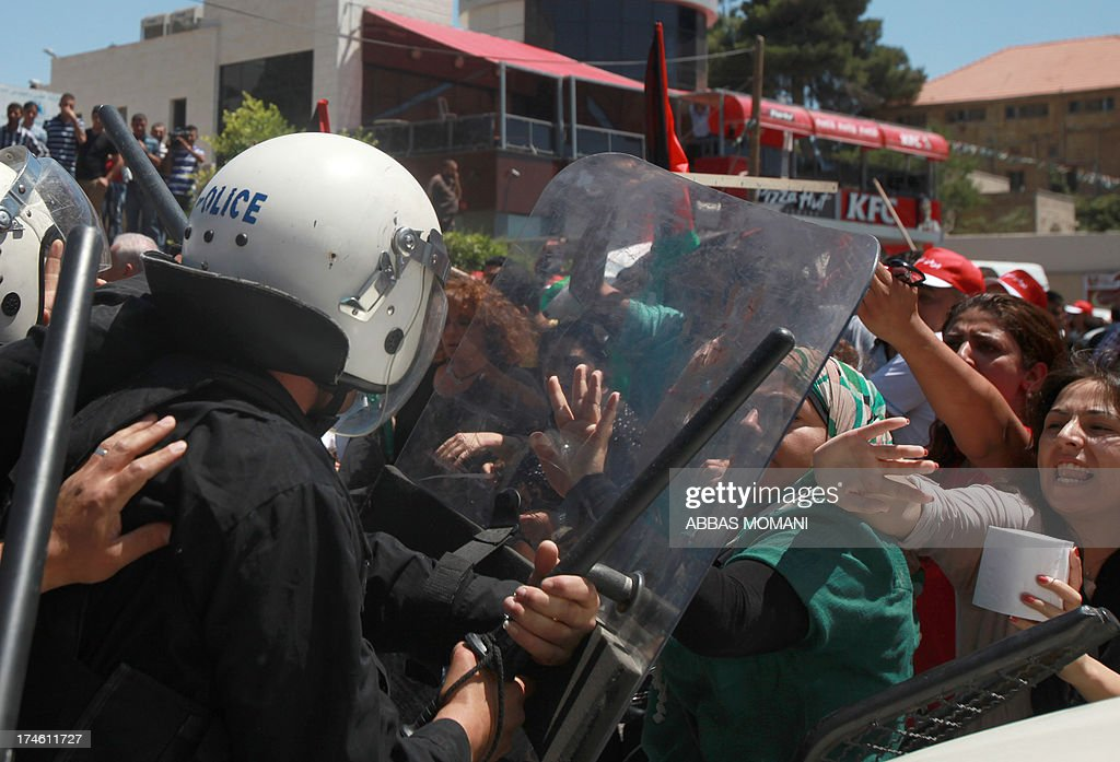 Palestinian protesters clash with riot police as they demonstrate against the upcoming negotiations between Palestinian leaders and Israel, in the West Bank city of Ramallah on July 28, 2013. A Palestinian official told AFP that the US-brokered renewal of peace talks, stalled since September 2010, would open in Washington this coming week.