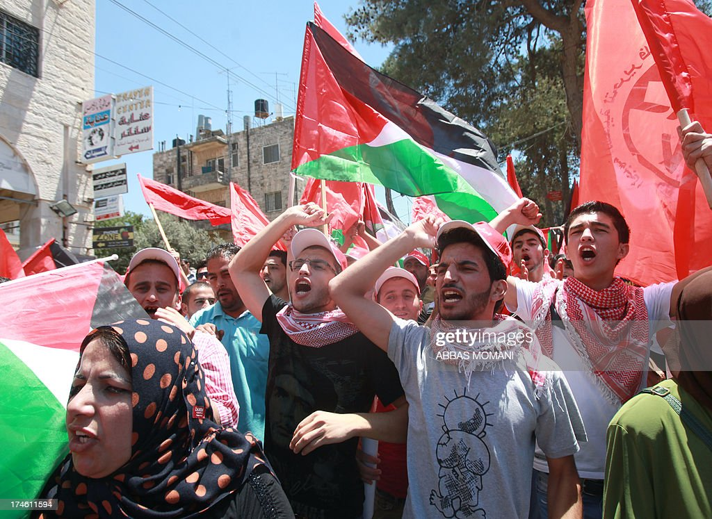 Palestinian protesters demonstrating against the upcoming negotiations between Palestinian leaders and Israel, march towards the headquarters of Palestinian president Mahmud Abbas, in the West Bank city of Ramallah on July 28, 2013. A Palestinian official told AFP that the US-brokered renewal of peace talks, stalled since September 2010, would open in Washington this coming week. AFP PHOTO/ABBAS MOMANI