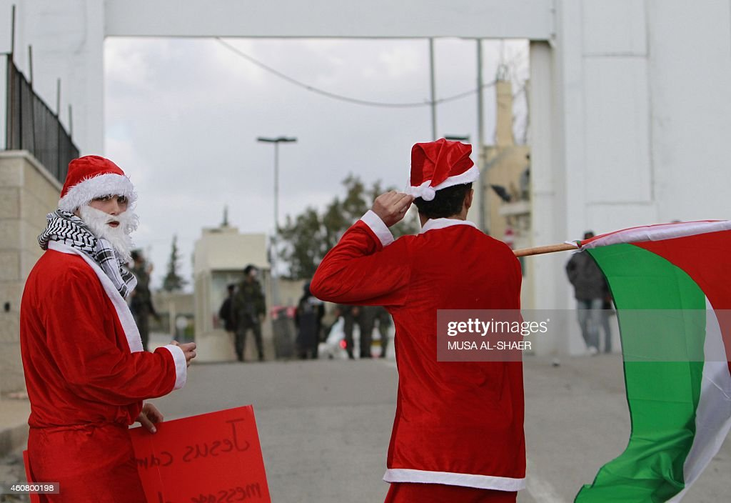 Palestinian protesters dressed in a Father Christmas costumes demonstrate in front of members of the Israeli security forces during a protest against...