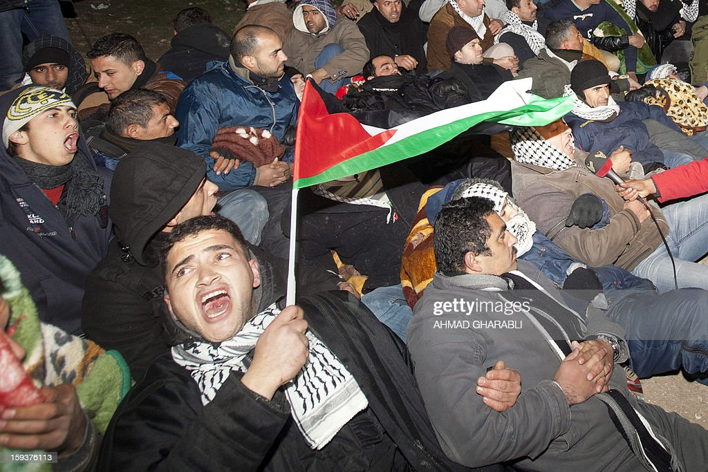 Palestinian protesters gather together as Israeli border police prepare to evict them from the scene in the controversial West Bank area known as E1 between Israeli annexed east Jerusalem and the settlement of Maaleh Adumim early on January 13, 2013. Israeli police early on January 13 evicted Palestinian protesters from a hilltop camp they set up in a West Bank area slated for Jewish settlement, police and witnesses said.