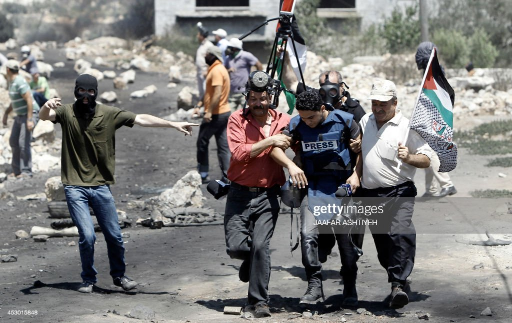 Palestinian protesters help a cameraman from the Palestinian TV, injured during clashes with Israeli security forces following a protest in the village of Kfar Qaddum, near the northern city of Nablus, in the occupied West Bank on August 1, 2014. A joint Palestinian delegation, including Hamas and Islamic Jihad, is to travel to Cairo on August 2, for ceasefire talks despite the renewed fighting in Gaza, president Mahmud Abbas's office announced.
