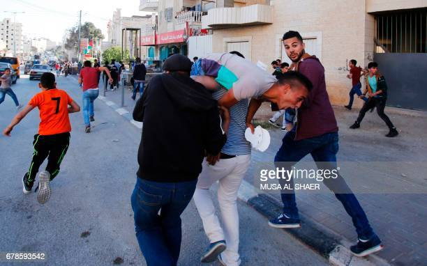 Palestinian protesters help an injured comrade during clashes with Israeli security forces following a demonstration in support of Palestinian...