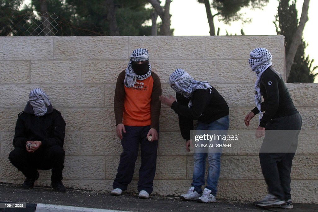 Palestinian protesters hide behind a wall as they ready to throw stones at an Israeli military observer tower during a protest in the Aida Palestinian refugee camp near the West Bank city of Bethlehem on January 13, 2013. Earlier, some 500 Israeli police moved to evacuate the West Bank Palestinian protest camp of Bab al-Shams, a tent village activists set up on January 11, in the controversial E1 area outside Jerusalem, several kilometers from Bethlehem.