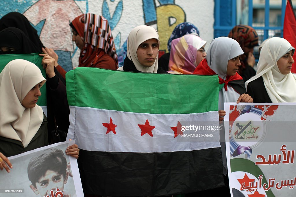 Palestinian protesters hold a pre-Baath Syrian flag, now used by the Free Syrian Army, during a demonstration in Gaza City in support of the Syrian people on February 5, 2013. Pressure mounted on Syrian President Bashar al-Assad to respond to a surprise offer of talks by his main political opponents aimed at ending warfare in which tens of thousands of people have died. AFP PHOTO / MAHMUD HAMS
