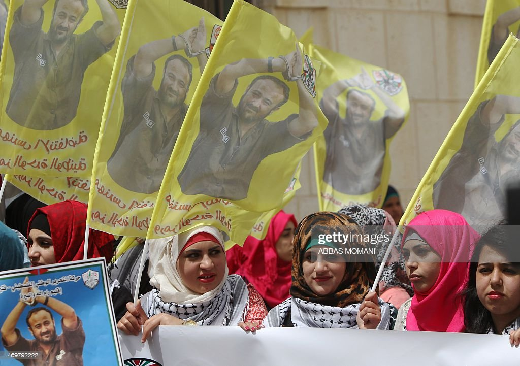 Palestinian protesters hold flags and placards bearing portraits of Fatah leader Marwan Barghuti, during a march to mark the anniversary of his arrest and demand his release from Israeli prison, in the West Bank city of Ramallah on April 15, 2015. Barghuti was sentenced to life imprisonment in 2002 for organizing anti-Israeli attacks during the Second Intifada in 2000.