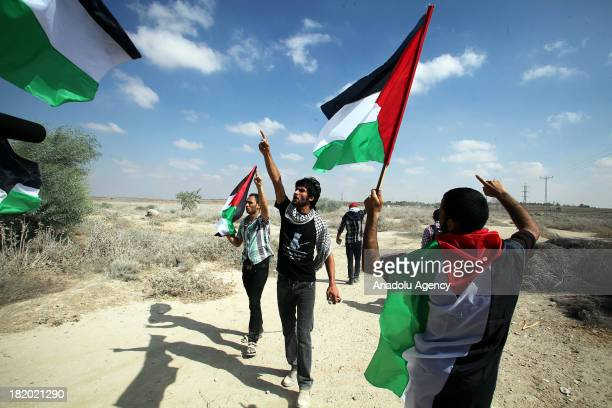 Palestinian protesters hold Palestinian flags and shout slogans during the clashes broke out on Gaza border on September 27 on the eve of the 13th...