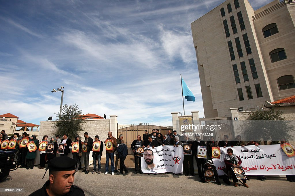 Palestinian protesters hold placards and banners during a demonstration in support with Palestinian prisoners held in Israeli jails, some of whom are observing a hunger strike, on January 24, 2012 outside the UN building in the West Bank city of Ramallah.