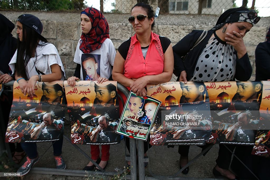 Palestinian protesters hold placards depicting portraits of Mohammed Abu Khdeir outside the district court in Jerusalem on May 3, 2016 as they await the verdict in the case of Israeli Yosef Haim Ben-David, the ringleader in the killing of the Palestinian teenager last year. Israeli prosecutors demanded a life sentence for a Jewish man found to be the ringleader of a group that beat and burned alive the Palestinian teenager in 2014. GHARABLI