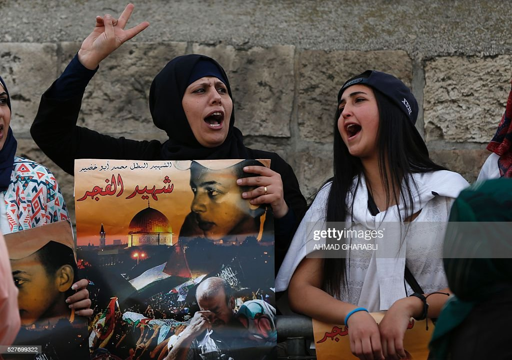 Palestinian protesters hold placards depicting portraits of Mohammed Abu Khdeir outside the district court in Jerusalem on May 3, 2016 as a life sentence is handed down to the ringleader of a Jewish gang who kidnapped, beat and burned alive a Palestinian teenager in 2014. An Israeli court handed down a life sentence to the ringleader of a Jewish gang who kidnapped, beat and burned alive a Palestinian teenager in 2014. Yosef Haim Ben-David, 31, was sentenced for killing 16- year-old Mohammed Abu Khdeir, and was also given 20 years for other crimes. Abu Khdeir was kidnapped by Ben-David and two young accomplices from Israeli-annexed east Jerusalem on July 2, 2014 and beaten. His burned body was found hours later in a forest in the western part of the city. / AFP / AHMAD