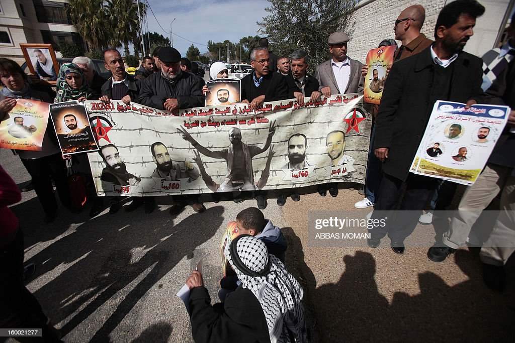 Palestinian protesters hold placards during a demonstration in support with Palestinian prisoners held in Israeli jails, some of whom are observing a hunger strike on January 24, 2012 outside the UN building in the West Bank city of Ramallah.