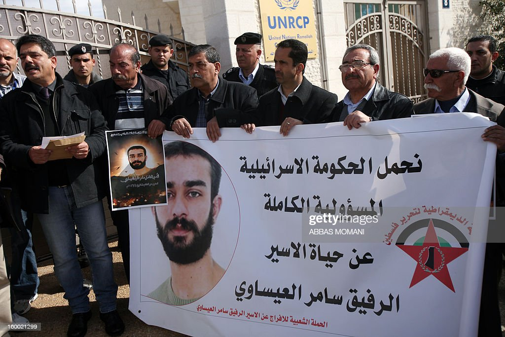 Palestinian protesters hold placards during a demonstration in support with Palestinian prisoners held in Israeli jails, some of whom are observing a hunger strike, on January 24, 2012 outside the UN building in the West Bank city of Ramallah. AFP PHOTO/ABBAS MOMANI