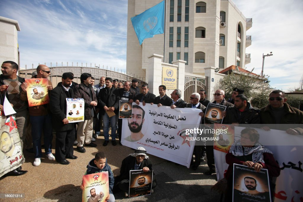 Palestinian protesters hold placards during a demonstration in support with Palestinian prisoners held in Israeli jails, some of whom are observing a hunger strike, on January 24, 2012 outside the UN building in the West Bank city of Ramallah.