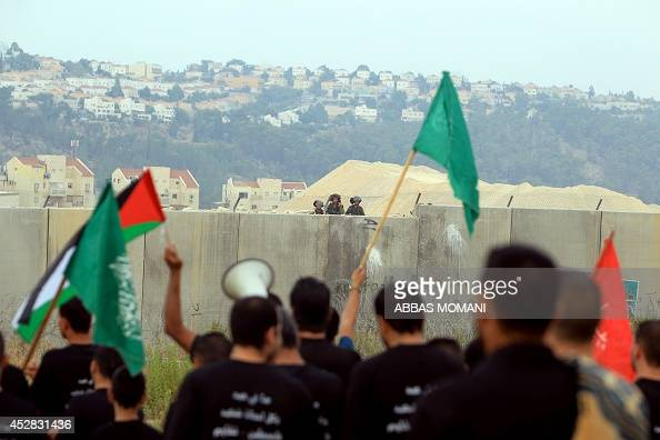Palestinian protesters holding national flags and the flag of the Islamist Hamas movement take part in a demonstration in front of the Israeli built...