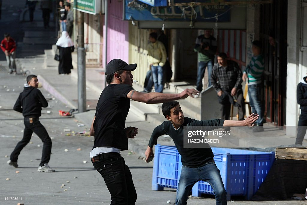 Palestinian protesters hurl rocks at Israeli police during clashes following increased security checks during the visit of Israeli Jews to the tomb of Othniel Ben Kenaz, considered holy by the Jewish faith, in the Palestinian side of the city of Hebron, on March 27, 2013. Religious Jews worldwide eat matzoth during the eight-day Pesach holiday that commemorates the Israelis' exodus from Egypt some 3,500 years ago and their ancestors' plight by refraining from eating leavened food products.