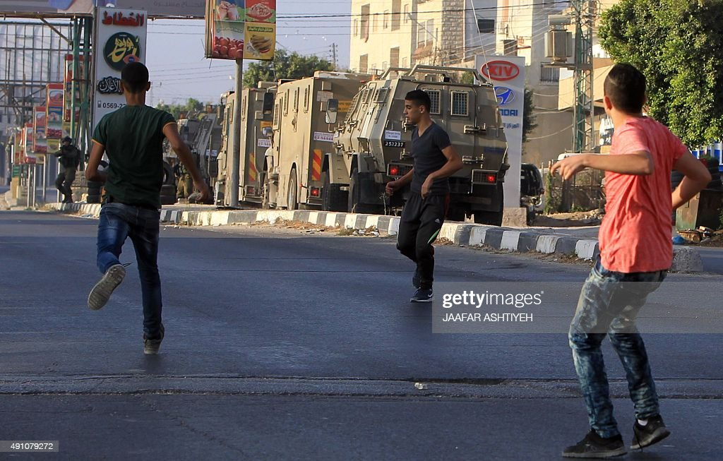 Palestinian protesters hurl rocks at Israeli soldiers on a street east of the West Bank city of Nablus on October 3 as they search for the suspected...