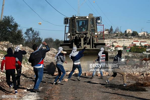 TOPSHOT Palestinian protesters hurl stones towards a digger operated by Israeli security forces during clashes following a demonstration against the...
