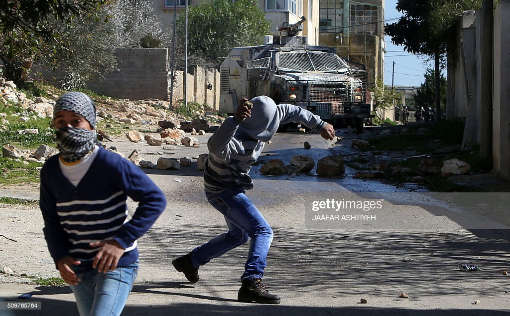 Palestinian protesters hurls rocks during clashes with Israeli soldiers following a demonstration against the expropriation of Palestinian land by Israel on February 12, 2016 in the village of Kfar Qaddum, near Nablus in the occupied West Bank. / AFP / JAAFAR ASHTIYEH
