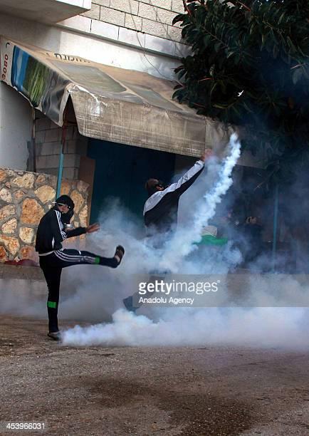 Palestinian protesters kick back tear gas canisters fired by Israeli security forces as clashes broke out during a demonstration against the...