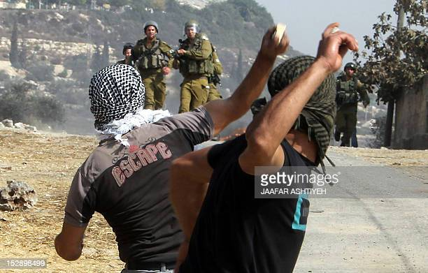 Palestinian protesters prepare to throw stones towards Israeli soldiers during a weekly demonstration against the expropriation of Palestinian land...