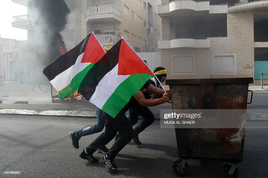 Palestinian protesters push a waste container during clashes with Israeli security forces on October 13 2015 in the West Bank city of Bethlehem A...