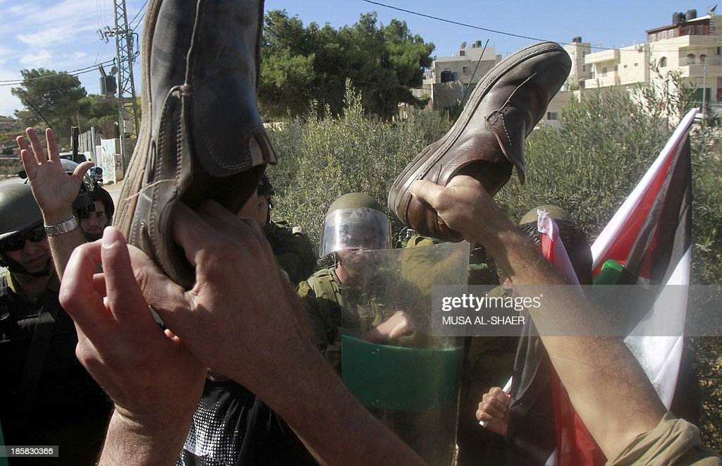 Palestinian protesters raise up shoes in front of Israeli soldiers as they take part in a weekly demonstration against the Israeli separation barrier and the expansion of Jewish settlements in the West Bank village of Maasarah, near Bethlehem, on October 25, 2013.