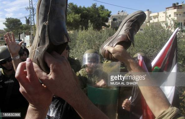 Palestinian protesters raise up shoes in front of Israeli soldiers as they take part in a weekly demonstration against the Israeli separation barrier...