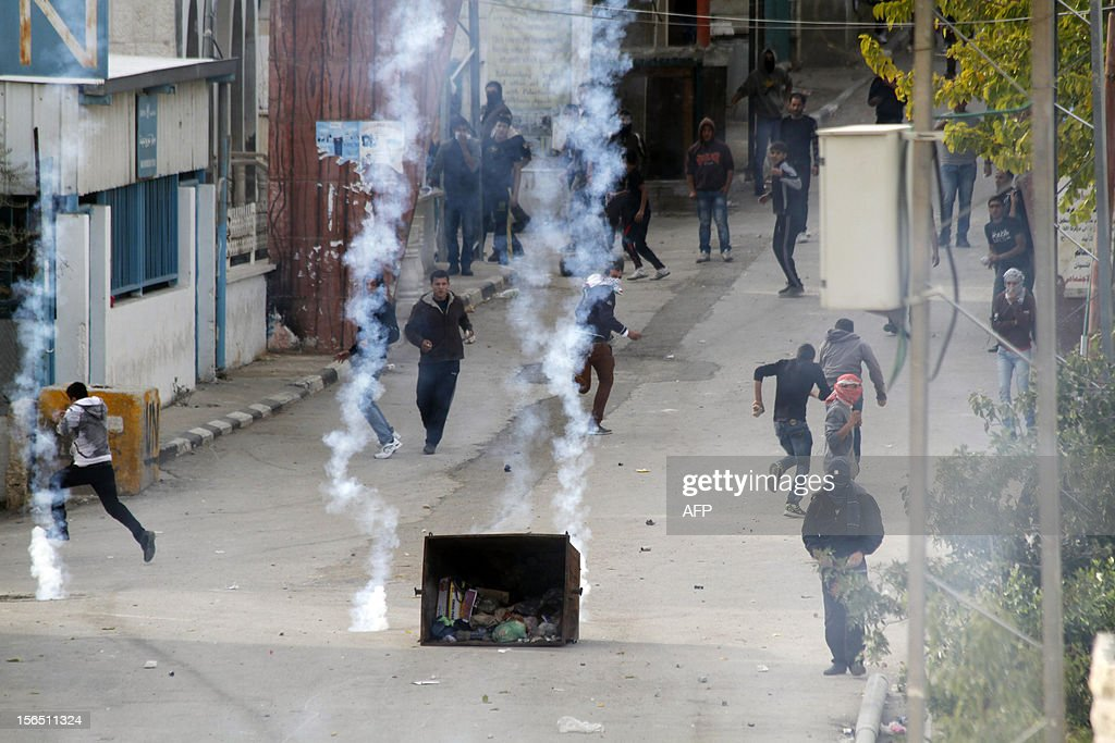 Palestinian protesters react as tear gas canisters fired by Israeli forces land next to them during a protest in Aida refugee camp near the West Bank city of Bethlehem on November 16, 2012. Thousands of angry Palestinians rallied across the West Bank, urging Hamas militants to 'bomb Tel Aviv' as Israel pursued a relentless air campaign on the Gaza Strip.