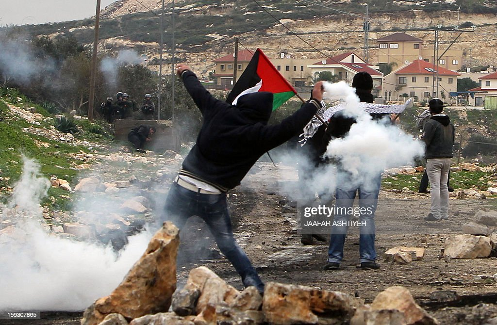 Palestinian protesters rethrow smoke devices during a protest against the expropriation of Palestinian land by Israel on January 11, 2013 in the village of Kafr Qaddum, near Nablus, in the occupied West Bank.