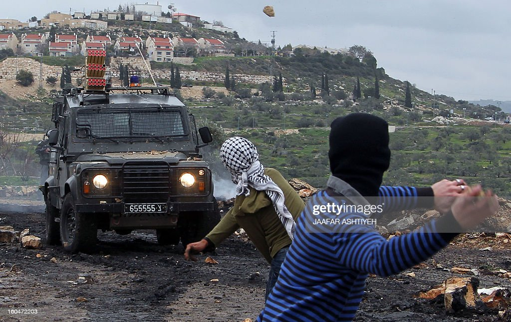 Palestinian protesters rethrow stones at israeli soldiers during clashes following a protest against the expropriation of Palestinian land by Israel on February 1, 2013 in the village of Kafr Qaddum, near Nablus, in the occupied West Bank.