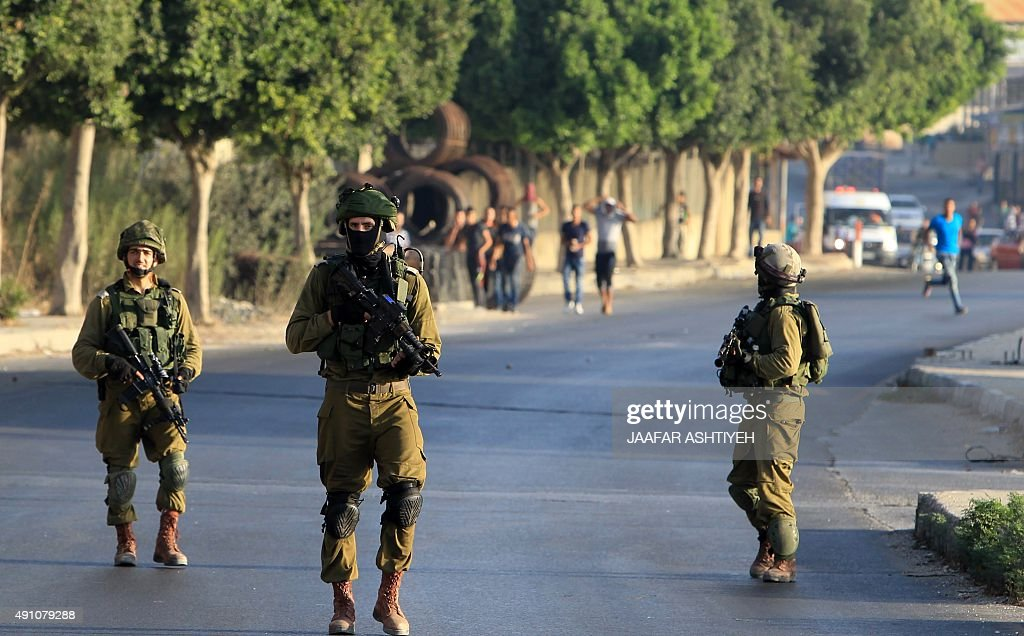 Palestinian protesters run after Israeli soldiers as they patrol a street east of the West Bank city of Nablus on October 3 during search for the...