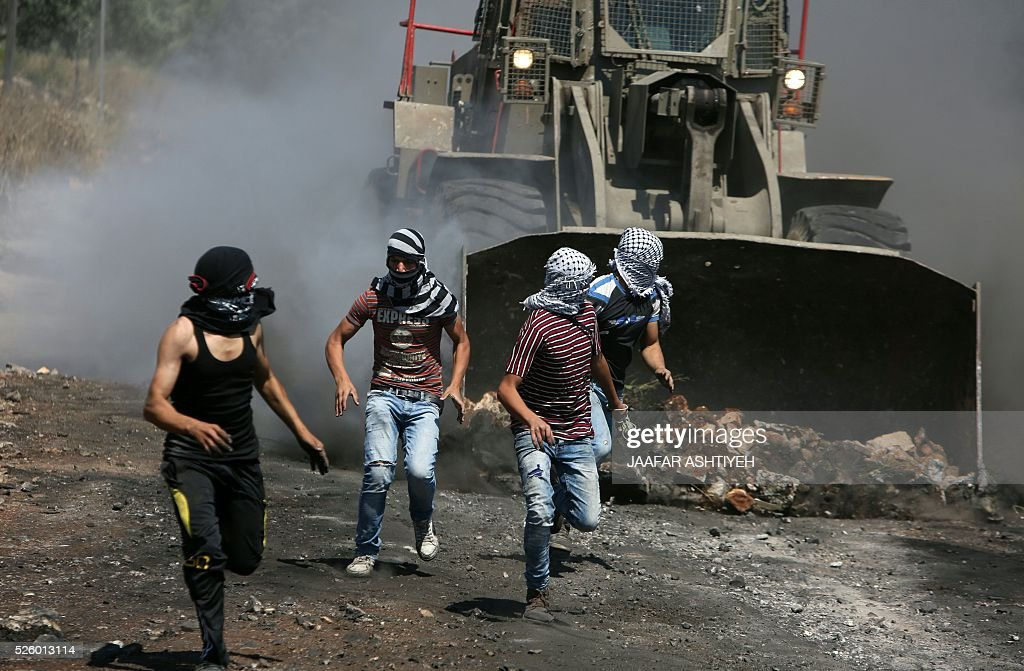 Palestinian protesters run away from a digger operated by Israeli security forces during clashes following a demonstration against the expropriation of Palestinian land by Israel on April 29, 2016 in the village of Kfar Qaddum, near Nablus, in the occupied West Bank. / AFP / JAAFAR