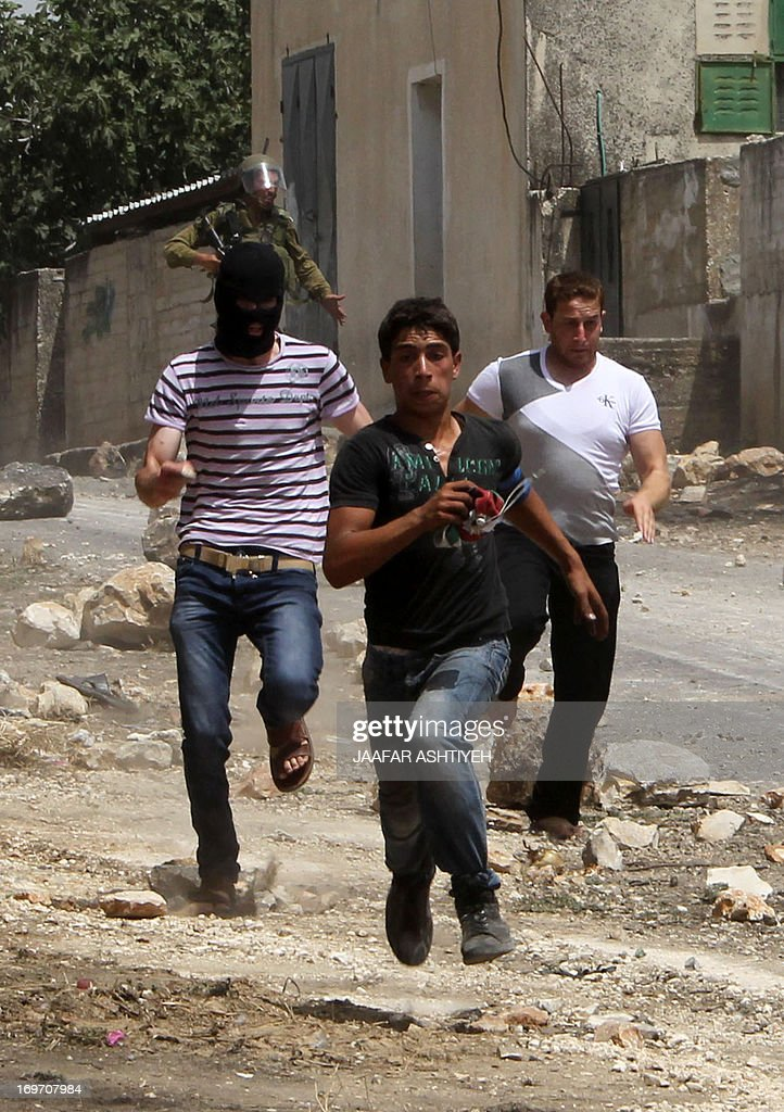 Palestinian protesters run away from Israeli soldiers during clashes following a protest against the expropriation of Palestinian land by Israel on May 31, 2013 in the village of Kfar Qaddum, near the occupied West Bank city of Nablus.