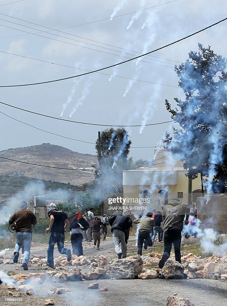 Palestinian protesters run away from tear gas canisters fired by Israeli security forces during clashes following a protest against the expropriation of Palestinian land by Israel in the village of Kfar Qaddum near Nablus in the occupied West Bank on April 19, 2013.