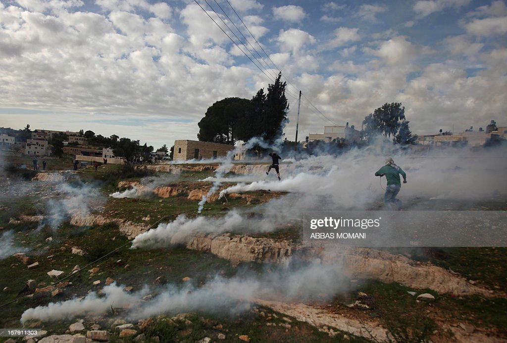 Palestinian protesters run away from tear gas during clashes with Israeli soldiers following a demonstration against the expropriation of Palestinian land by Israel in the West Bank village of Nabi Saleh on December 7, 2012.