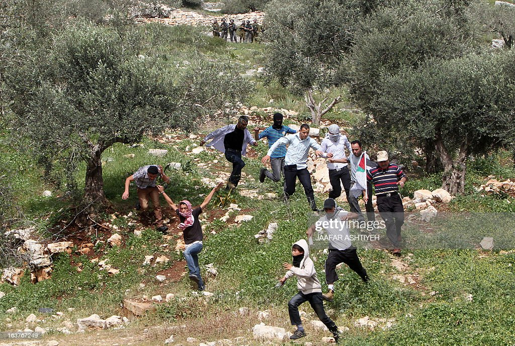 Palestinian protesters run for cover during clashes following a protest against the expropriation of Palestinian land by Israel on March 15, 2013, in the village of Kafr Qaddum, near the occupied West Bank city of Nablus. AFP PHOTO/JAAFAR ASHTIYEH