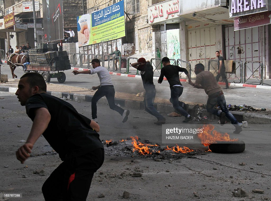 Palestinian protesters run for cover during clashes with Israeli border policemen in central Hebron in the occupied West Bank on March 15, 2013 following a protest against Israeli occupation and the expansion of Jewish settlements.
