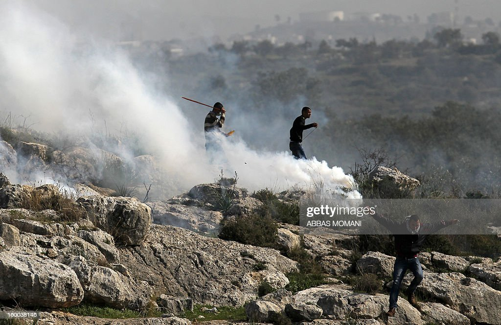 Palestinian protesters run for cover from tear gas fired by Israeli troops during a demonstration against the expansion of Jewish settlements on Palestinian land in the village of Budrus, west of the West Bank city of Ramallah, on January 25, 2013.