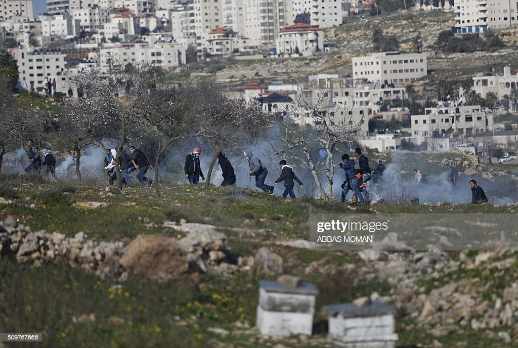 Palestinian protesters run for cover from tear gas fired by Israeli forces during clashes that followed a demonstration on February 12, 2016 in solidarity with Palestinian prisoners held in Israeli jails, outside the compound of the Israeli-run Ofer Prison near Betunia in the occoupied West Bank. / AFP / ABBAS MOMANI
