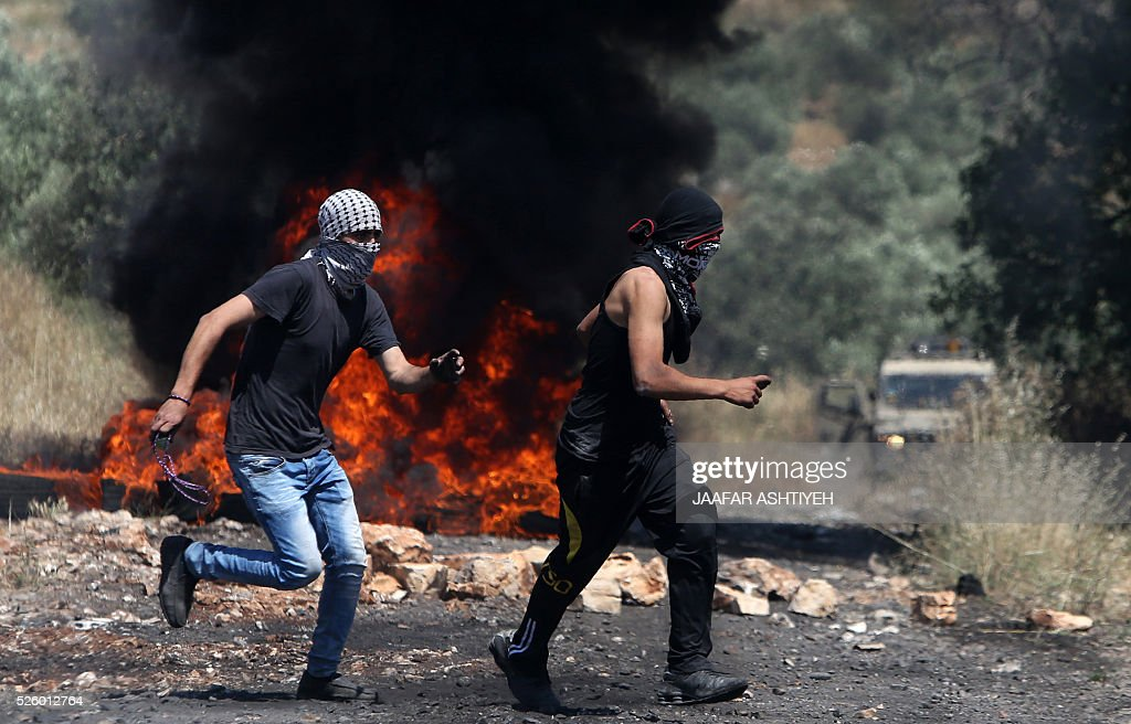 Palestinian protesters run in front of burning tires during clashes with Israeli security forces following a demonstration against the expropriation of Palestinian land by Israel on April 29, 2016 in the village of Kfar Qaddum, near Nablus, in the occupied West Bank. / AFP / JAAFAR
