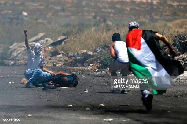 Palestinian protesters run to help a fellow demonstrator after he was injured during clashes with Israeli security forces following a protest marking...