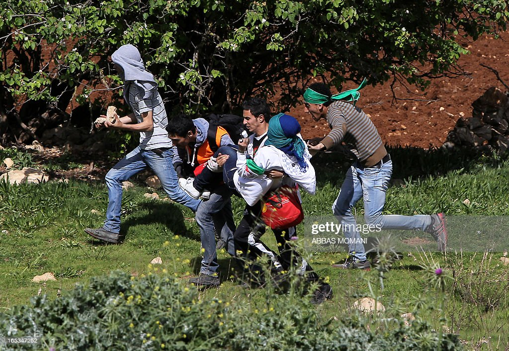 Palestinian protesters run while carrying an injured demonstrator during clashes with Israeli security forces outside Ofer prison near the West Bank city of Ramallah on April 3, 2013 following a pr...