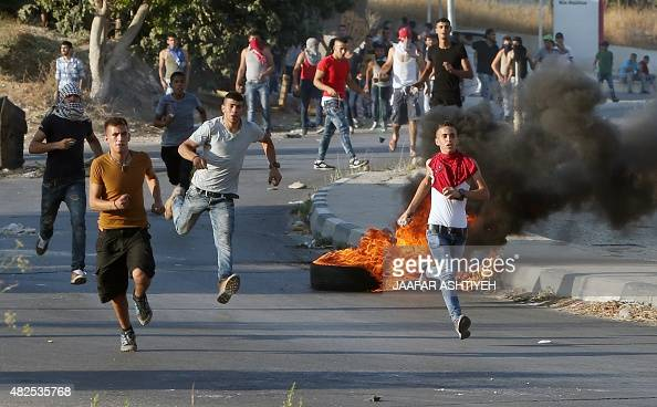 Palestinian protesters run with stones during clashes with Israeli security forces on July 31 2015 at the Israelimaned Hawara checkpoint south of the...