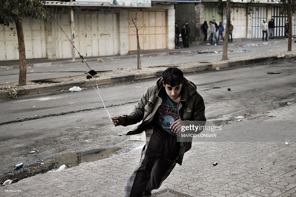 A Palestinian protesters runs to hide in a hallway during clashes with the Israeli Army in the West Bank town of Hebron on February 25, 2013. Thousands of mourners attended a tense funeral in the West Bank of a prisoner Palestinians say was tortured to death in an Israeli jail, as masked militants vowed vengeance.