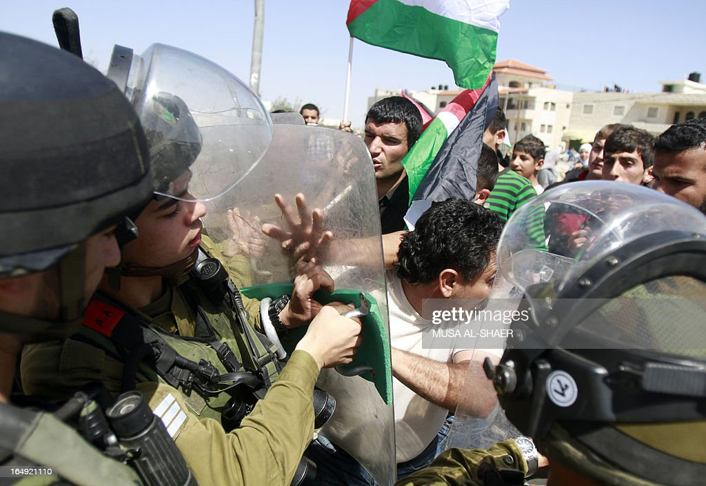 Palestinian protesters scuffle with Israeli soldiers following a weekly demonstration against the Israeli separation barrier and the expansion of Jewish settlements, in the West Bank village of Maasarah, near Bethlehem, on March 29, 2013. Israel deployed significant security reinforcements in the occupied West Bank including east Jerusalem for demonstrations commemorating the deaths in 1976 of Arab Israelis on 'Land Day'.