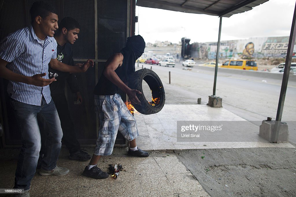 Palestinian protesters set a tire on fire during clashes with the Israeli army during Nakba day on May 15, 2013 near the Qalandia checkpoint at the outskirts of Ramallah, the West Bank. Palestinians mark Israel's establishment in 1948 with 'Nakba' or 'catastrophe' day on May 15, to remember the thousands of Palestinians who fled or were expelled during the creation of the Jewish state and the subsequent war.